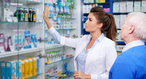 Female pharmacist helping an older man